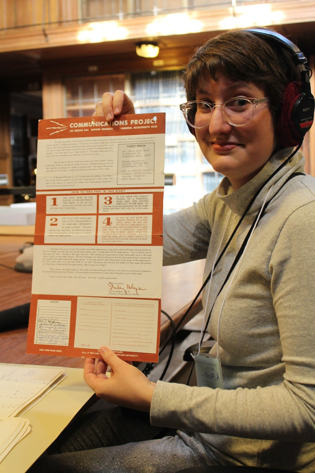 Producer Annie Minoff, with headphones on, holds up an old letter experiment.