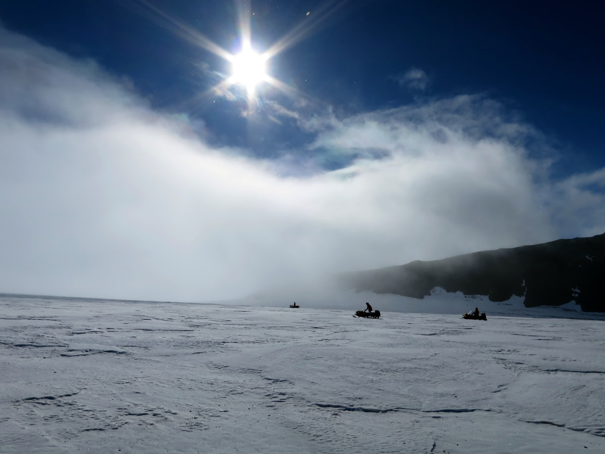 a landscape shot of the scientists on snowmobiles.