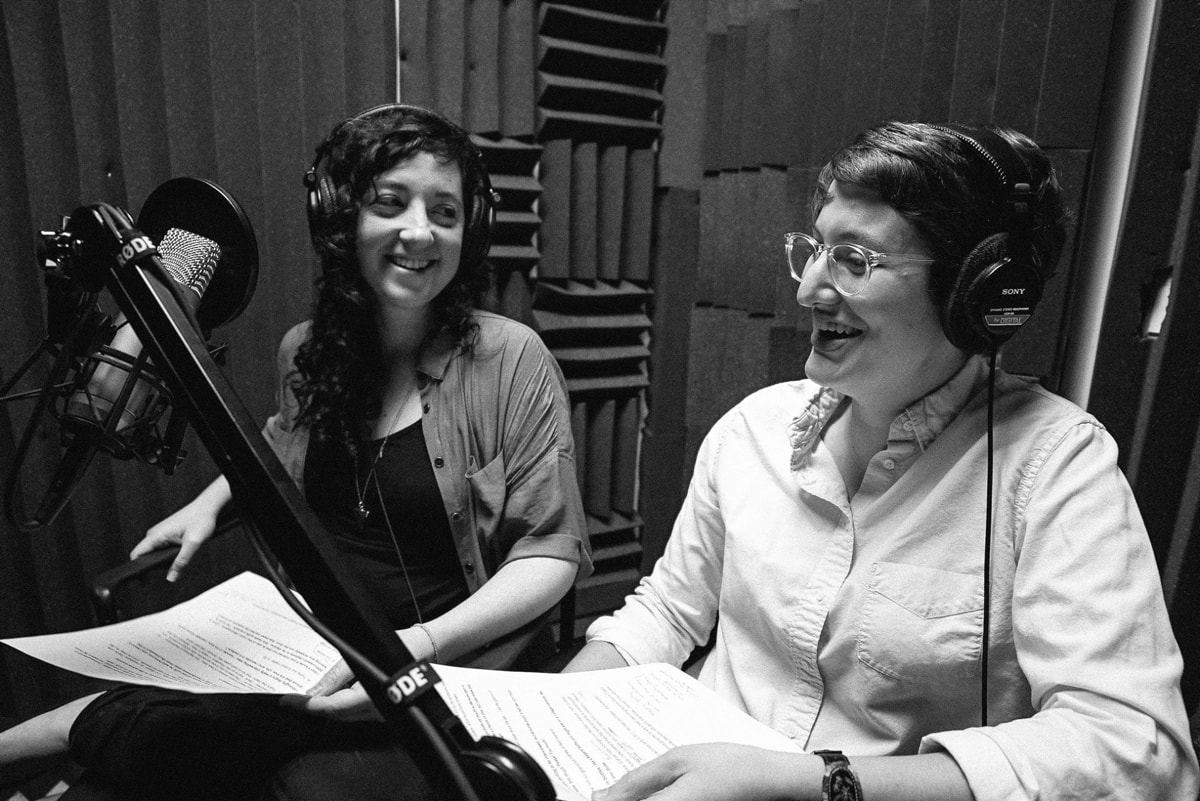 Elah and Annie with headphones and a mic in a studio with soundproofed walls.
