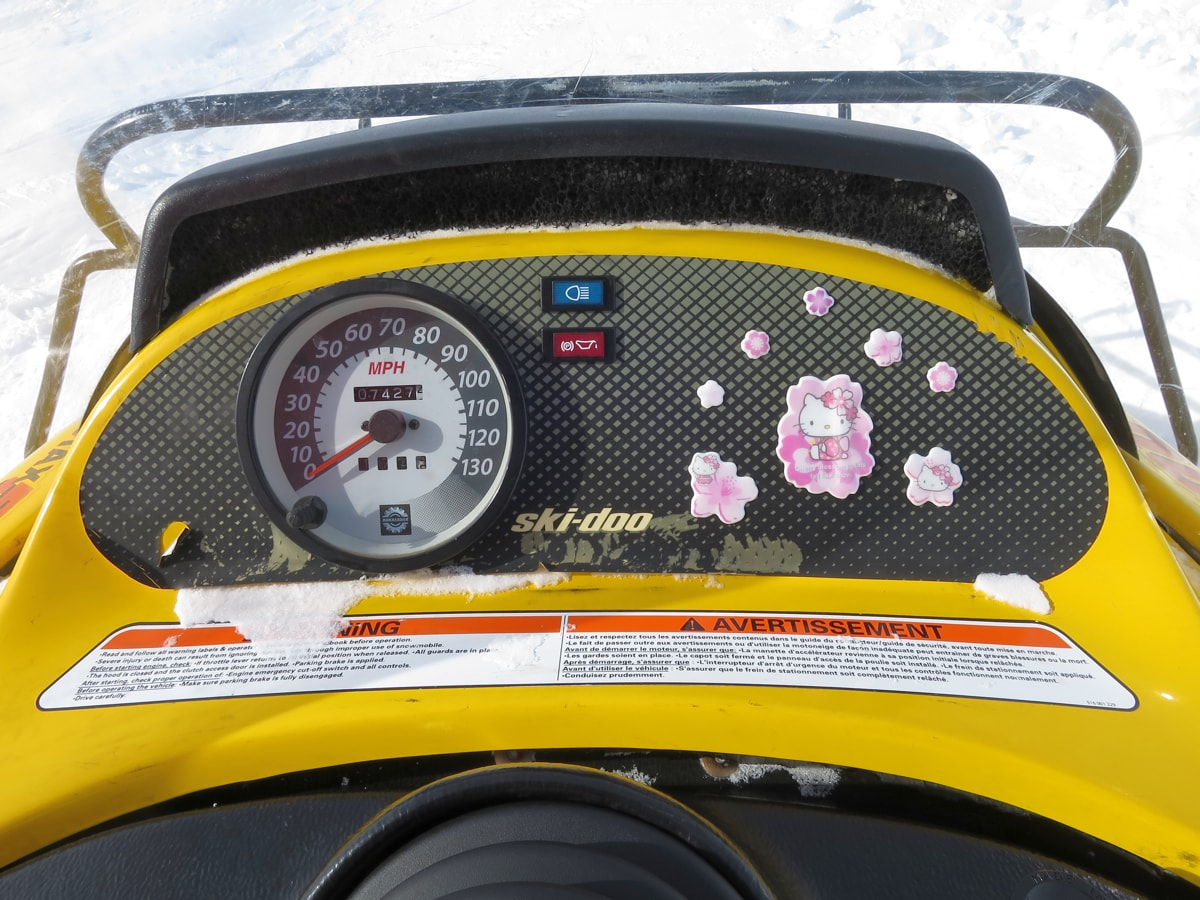 the dashboard of a snowmobile that has hello kitty stickers next to the speedometer.