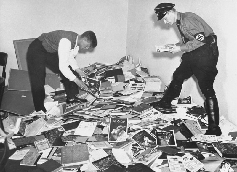 A German student and Nazi officer sift through a gigantic pile of books and photographs.